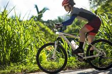 Woman Riding Bike Down A Slope...