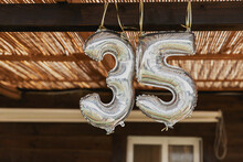 Happy 35th Birthday Party Celebration Balloon. Silver Number Thirty Five 35 Made Of Inflatable Balloon With Golden Ribbon Isolated On Blurred Brown Background Outdoor. Composition Of Balloons