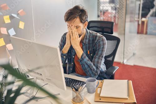 Fototapeta Tired young man working in modern office obraz na płótnie