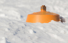 A Fire Hydrant Almost Completely Buried In A Snowbank. The Top Is Yellow, The Rest Is Not Visible. The Foreground And Background Is Snow. Focus Is On The Square Valve Stem On Top. Room For Text.