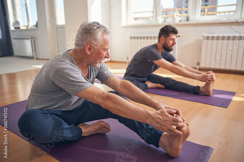 Obraz Beginner yogi and his coach practicing yoga - fototapety do salonu