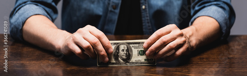 Fototapeta Panoramic crop of man holding dollar banknotes at table isolated on grey obraz
