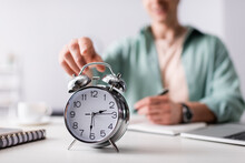 Selective Focus Of Man Pulling Hand To Alarm Clock Near Laptop And Notebooks On Table, Concept Of Time Management
