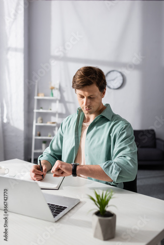 Selective focus of freelancer writing on notebook and looking at wristwatch near laptop on table, concept of time management