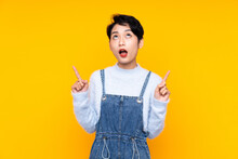 Young Asian Girl In Overalls Over Isolated Yellow Background Pointing With The Index Finger A Great Idea