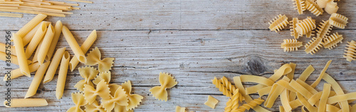Photographie a lot of different kinds of egg noodles and yellow pasta on wooden background