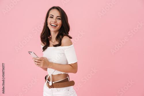 Fototapeta Image of joyful brunette woman using cellphone and laughing obraz