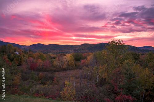Valokuvatapetti Stunning sunset over forested mountains during the peak of autumn colour season