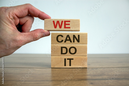Fototapety, obrazy: Male hand placing a block with word 'we' on top of a blocks tower with words 'can do it'. Wooden table. Beautiful white background. Copy space.