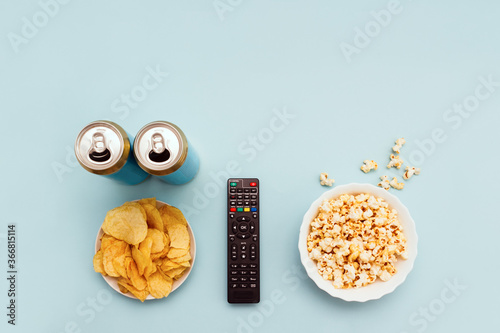 Fotografering Remote control, snacks and cans of beer on blue background