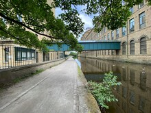 A Green Painted Corridor, Suspended Above The Leeds To Liverpool Canal, Connecting Two Victorian Mills In The Village Of Saltaire, Bradford, UK