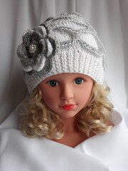 Unique hand knitted ladies hat, white-gray color, decorated with a crocheted flower.