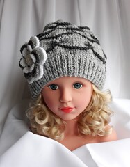 Unique hand knitted ladies hat, gray-white color, decorated with a crocheted flower.