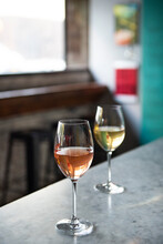 Two Glasses Of Wine On A Bar