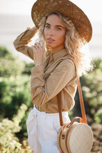 Outdoor Portrait Of Young Beautiful Curly Hair Lady Wearing Straw Hat, Holding Wicker Round Rotang Bag, Posing On Nature Background. Outdoor Summer Portrait Of Fashionable Happy Smiling Blonde Woman