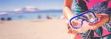Woman Holding Snorkel Googles Against Blurred Beach. Diving Goggles Best Fun For Summer Holiday.
