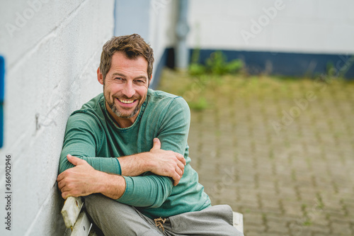 Mann sitzt entspannt auf einer Bank, und sieht positiv nach vorne,im Hintergrund Fotobehang