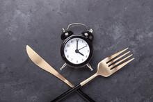Black Alarm Clock, Fork, Knife On Dark Stone Background. Intermittent Fasting Concept