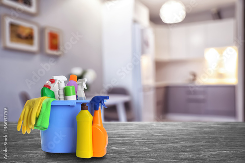 Fotomural Bucket with cleaning supplies on stone surface in modern room