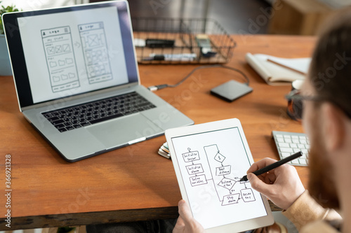 Fotografiet Over shoulder view of man using digital tablet and stylus and drawing scheme for