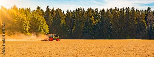 Fototapeta Sommer auf dem Land / Landwirtschaft Ernte Wald Hintergrund Banner Panorama: Alter Traktor beim Fräsen von Stroh Getreide Gersten Weizen Feld, mit aufgewirbeltem Staub, im Schwarzwald, Deutschland obraz