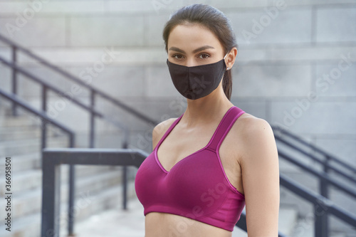 Portrait of a young caucasian fitness woman wearing protective face mask looking at camera while running outdoors during coronavirus pandemic - 366958501