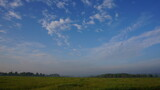 blue sky with clouds and a field