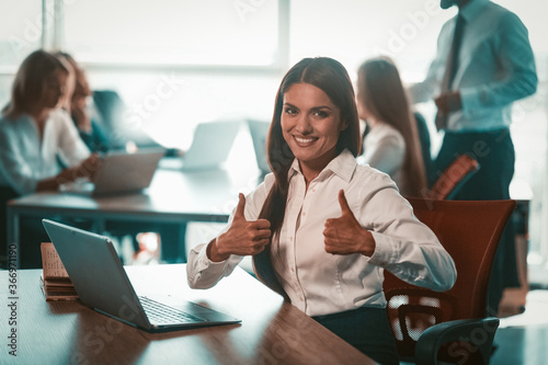 Valokuva Businesswoman shows thumbs up in office