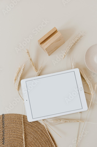 Tablet pad with blank screen on wheat / rye stalks and wicker napkin on beige background. Flat lay, top view mockup copy space template