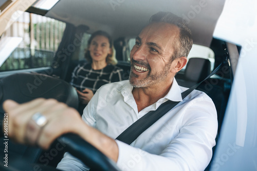 Valokuvatapetti Taxi driver talking to a female passenger in car