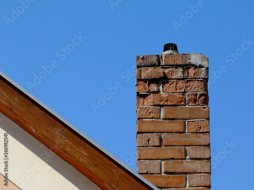 Obraz na plátne Isolated clay brick chimney with weathered and spalling surface
