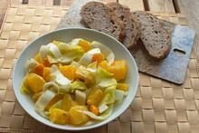 Ein Salatteller Mit Geschnittenen Chicoree, Orangen,  Physalis, Sonnenblumen- Und Kürbiskerne Neben Einem Schneidebrett Auf Dem Drei Scheiben Walnuss Brot Liegen.