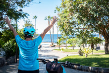 Rear View Of A Woman With Electrice Bicycle And Helmet Resting After Excursion With Raised Arms - Public Park With Palm Trees And Horizon Over Water - Healthy Lifestyle For Retired People