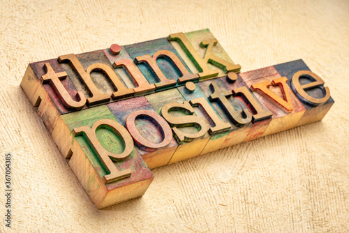 Obraz Think positive - word abstract in vintage letterpress wood type blocks against textured handmade paper, optimism, positivity and mindset concept - fototapety do salonu