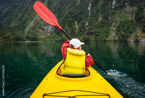 Photo Young boy in bright yellow kayak on mountain lake.