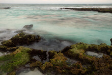 Long Exposure Shot Of The Beach At Sunset. Surreal Water Smoky Effect. View Of The Shore Mossy Rocks, Turquoise Ocean Water And Blurred Sea Waves With A Beautiful Dusk Light.