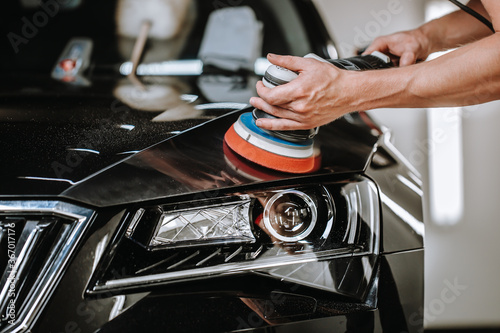 Fototapeta Professional detailing a car in car studio, hands with orbital polisher, scratching remover, vehicle care concept obraz