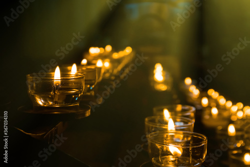 Obraz closeup row of lamp in the church in the rays of light - fototapety do salonu