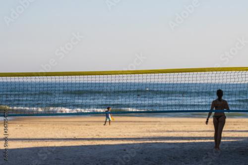 Rede de vôlei armada na praia com sombra de mulher em segundo plano Fototapet