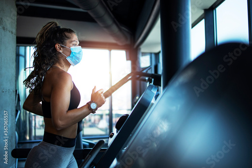 Obraz na płótnie Sportswoman training on treadmill in gym and wearing face mask to protect herself against coronavirus during global pandemic of covid-19 virus