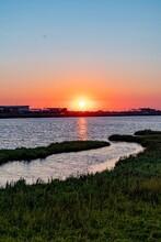 Sunset Over Water And Marshlan...
