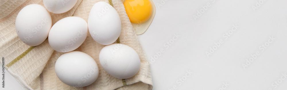 Fototapeta Lots of eggs and a broken egg on the tea towel.