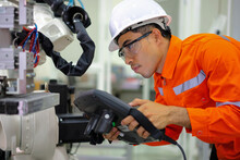 Smart Factort Concept: An Engineer Use Handheld Controller Setting Industrial Robot In Productionplant.
