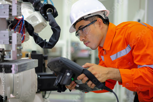 Photo Smart factort concept: An engineer use handheld controller setting industrial robot in productionplant
