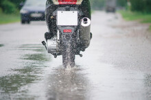 Motorcycle Moped Rides Through A Puddle On A Wet Road In The Rain. Spray Is Flying From The Wheels. Close-up