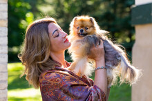 Medium Horizontal Back Lit Portrait Of Beautiful Young Woman Holding Up Her Petite Orange Sable Pomeranian Dog In Exterior Garden Location During A Summer Late Afternoon