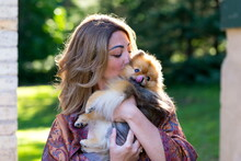 Medium Horizontal Back Lit Portrait Of Beautiful Young Woman Holding And Kissing Her Petite Orange Sable Pomeranian Dog In Exterior Garden Location During A Summer Late Afternoon