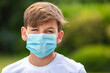 Boy teenager teen male child wearing face mask outside in the Coronavirus COVID-19 pandemic