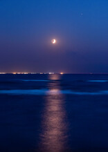 Vertical Seascape With Seasparkle And A Waxing Crescent Moon In The Sky.