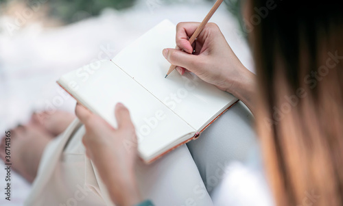 Young female writing on notepad with pencil while sitting outdoor Canvas-taulu